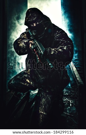 Soldier holding his rifle with laser turned on ready to shoot