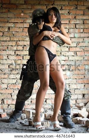 Soldier holding pretty woman in bikini hostage - stock photo