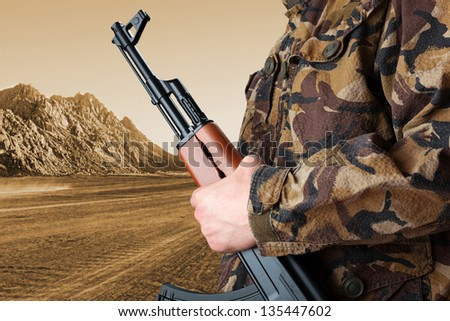 Soldier holding rifle AK-47 against desert - stock photo