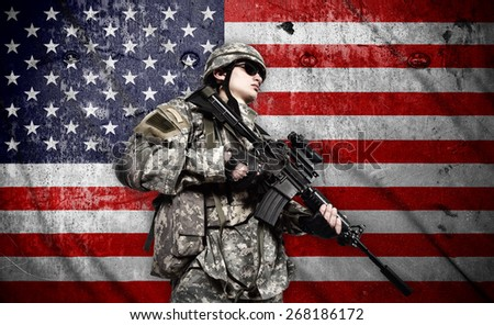 soldier holding rifle on a american flag background - stock photo