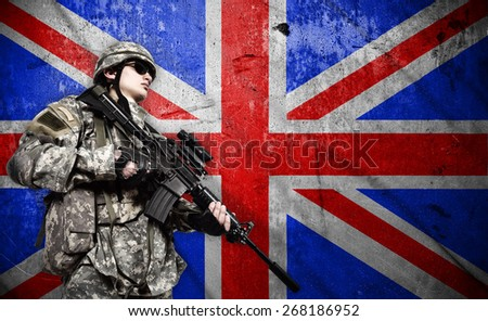 soldier holding rifle on a England flag background - stock photo