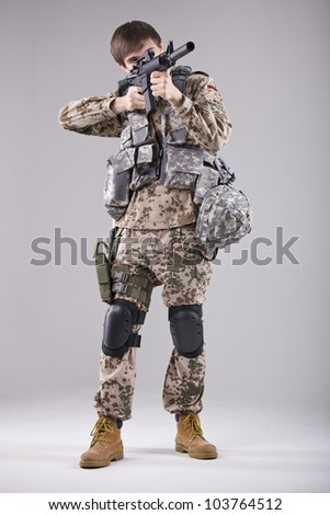 Soldier in camouflage aiming with machine gun in a white studio - stock photo