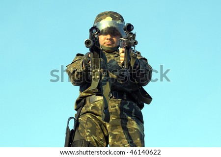 Soldier in camouflage and helmet with two guns