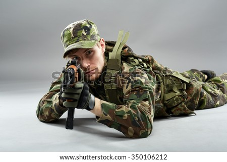 Soldier in camouflage uniform aiming the target from laying down position - stock photo