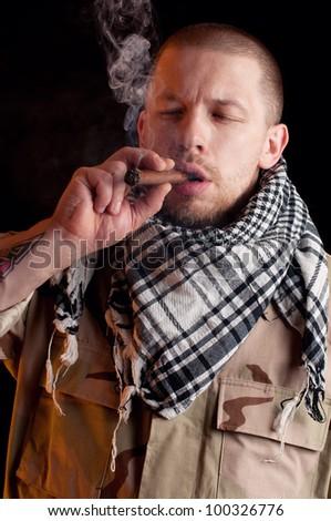 Soldier in combat uniform smoking cigar, dark background - stock photo