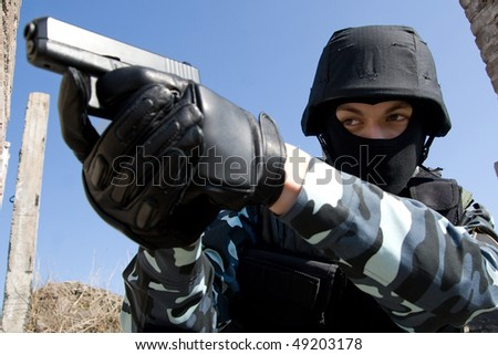 Soldier in full ammunition aiming the target with a semi-automatic 9mm glock pistol - stock photo
