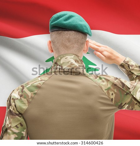 Soldier in hat facing national flag series - Lebanon - stock photo