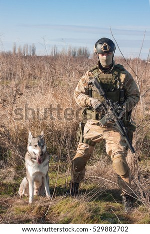 Soldier in nato uniform posing in fields with dog