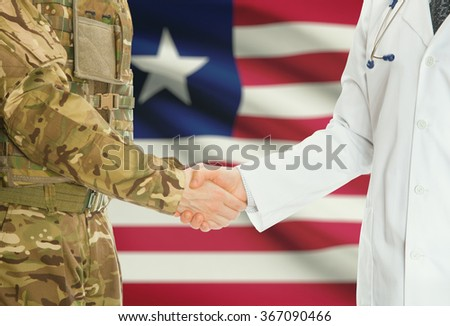 Soldier in uniform and doctor shaking hands with national flag on background - Liberia