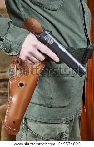 Soldier in uniform holding a gun Colt near holster - stock photo