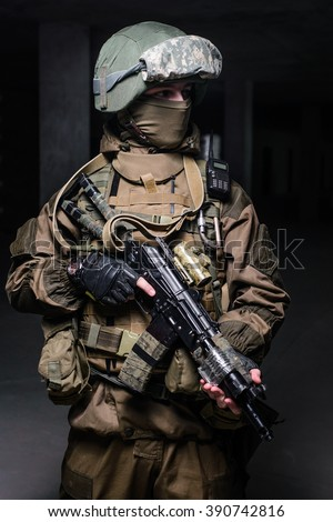 Soldier in uniform with helmet, gun in hand and special equipment on dark background/Special forces soldier with rifle on dark background