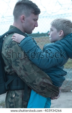 Soldier leaving for army holds his son on goodbye  - stock photo