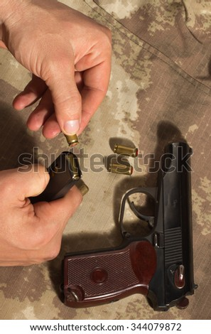 Soldier load ammo in the clip Makarov pistol. Clouse up - stock photo