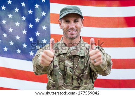 Soldier looking at camera thumbs up against an american flag - stock photo