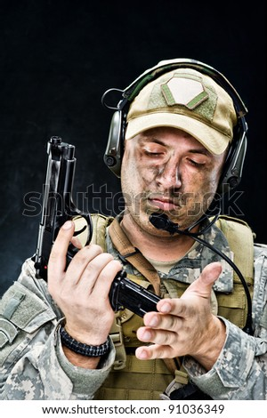 Soldier of USA army posing with a gun on a black background - stock photo