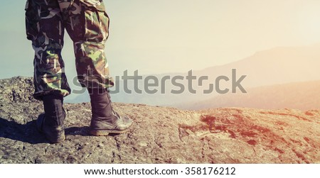 Soldier on the top of a mountain - stock photo