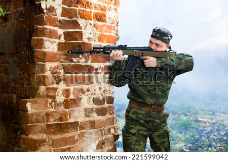 Soldier or militiaman in camouflage with assault rifle  fighting in ruins - stock photo