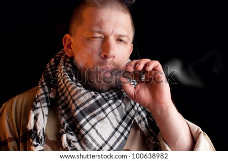 Soldier puffing some good cigar smoke, black background - stock photo