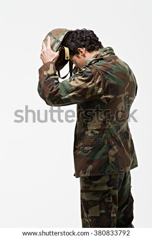 Soldier putting on helmet - stock photo