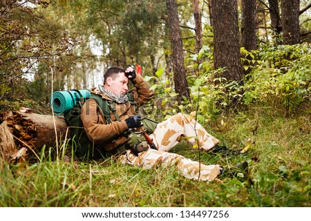 Soldier relaxing in a forest. - stock photo