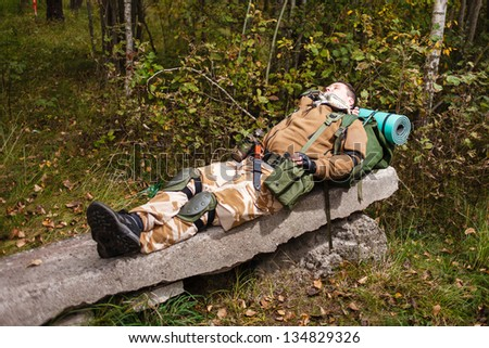 Soldier relaxing on reinforced concrete slab. - stock photo