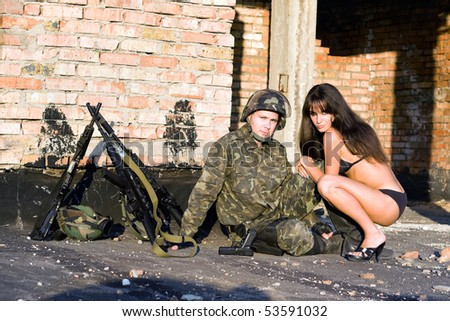 Soldier resting with sexy playful young woman - stock photo