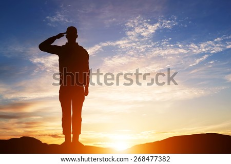 Soldier salute. Silhouette on sunset sky. War, army, military, guard concept. - stock photo