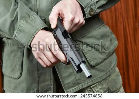 Soldier shutter cocking pistol gun Colt - stock photo