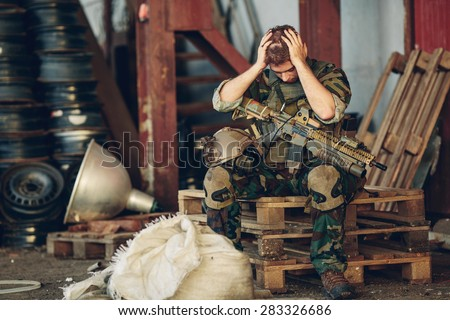soldier sitting with arms and hands holding her head - stock photo