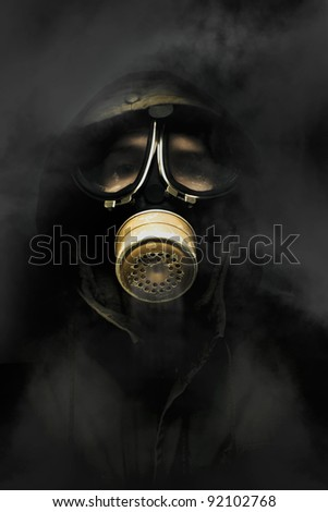 Soldier Standing In The Dead Of Night Breathing Through A Military Issued Gasmask While A Haze Of Toxic Gas And Smoke Circulate Around The Air - stock photo