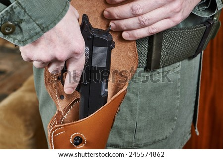 Soldier takes out a gun out of the holster - stock photo