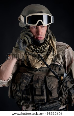 Soldier talking at the radio against black background. - stock photo