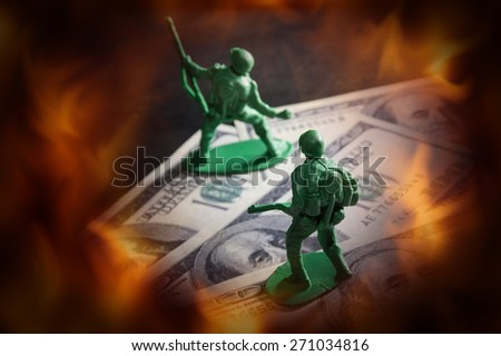 Soldier toys on money with fire screen. - stock photo