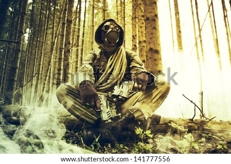 Soldier wearing a gas mask with guns - stock photo