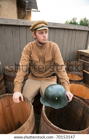 Soldier with a helmet sitting on the butt. Costume accord the times of World War I. Photo made at cinema city Cinevilla in Latvia. - stock photo