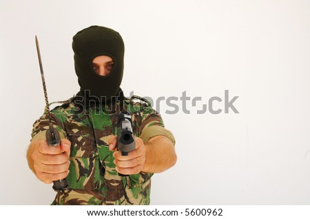 soldier with a military mask holding knife and a pistol - stock photo