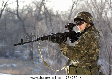 Soldier with a sniper rifle in his hands - stock photo