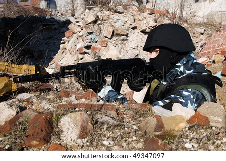 Soldier with automatic rifle shooting from covered position - stock photo