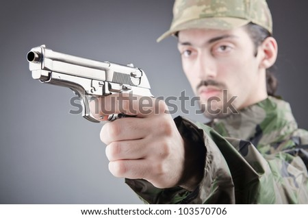 Soldier with gun in studio shooting - stock photo