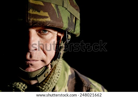 Soldier With Half Face In Shadow - stock photo