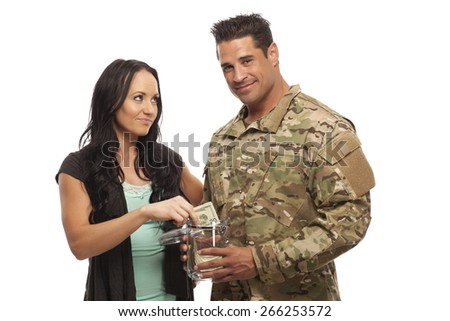Soldier with his wife collecting money in glass jar - stock photo