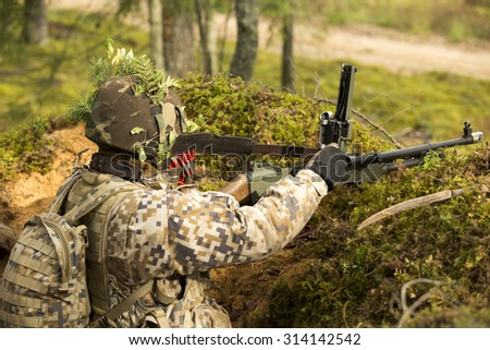 Soldier with machine gun on the position - stock photo