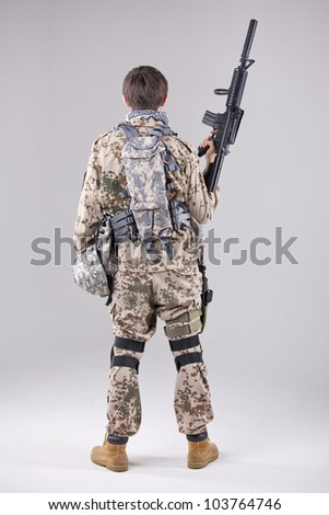 Soldier with machine gun - shot from behind over white - stock photo