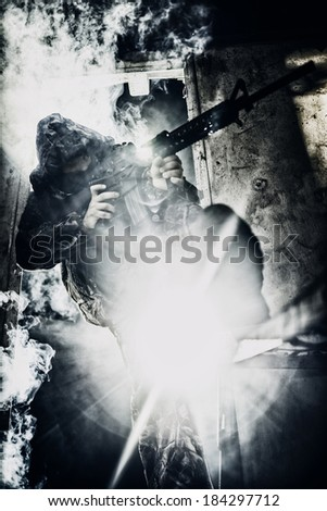 Soldier with rifle aiming against strong light covered in smoke