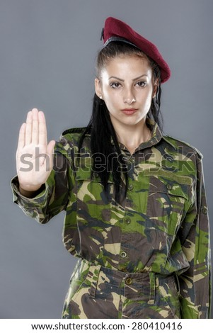Soldier woman showing palm stop sign on gray background - stock photo