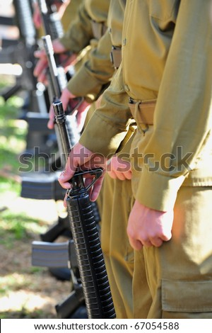 Soldiers in army uniform line up holding guns - stock photo
