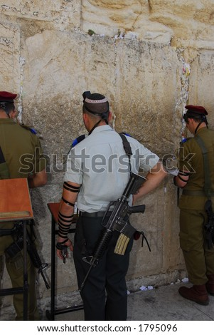 Soldiers praying at the Western Wall - stock photo