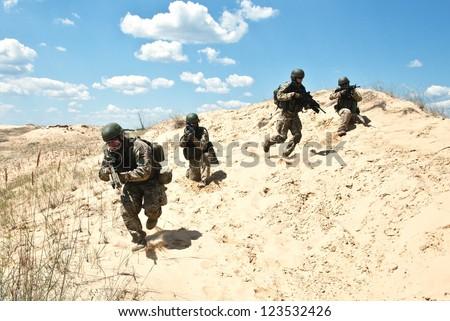 soldiers running through the desert - stock photo