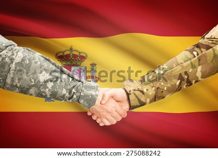 Soldiers shaking hands with flag on background - Spain - stock photo