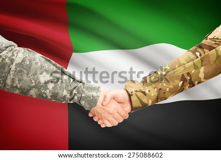 Soldiers shaking hands with flag on background - United Arab Emirates - stock photo